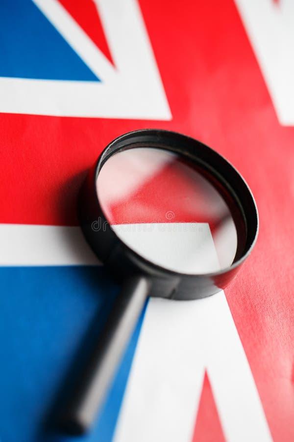 Bandeira BRITÂNICA que olha através de uma lupa Espiando e observando Inglaterra Monitorando o estado de Grâ Bretanha o conceito  foto de stock