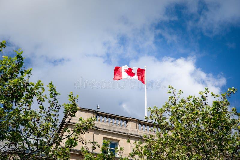 Bandeira canadense de ondula??o contra o c?u azul imagens de stock