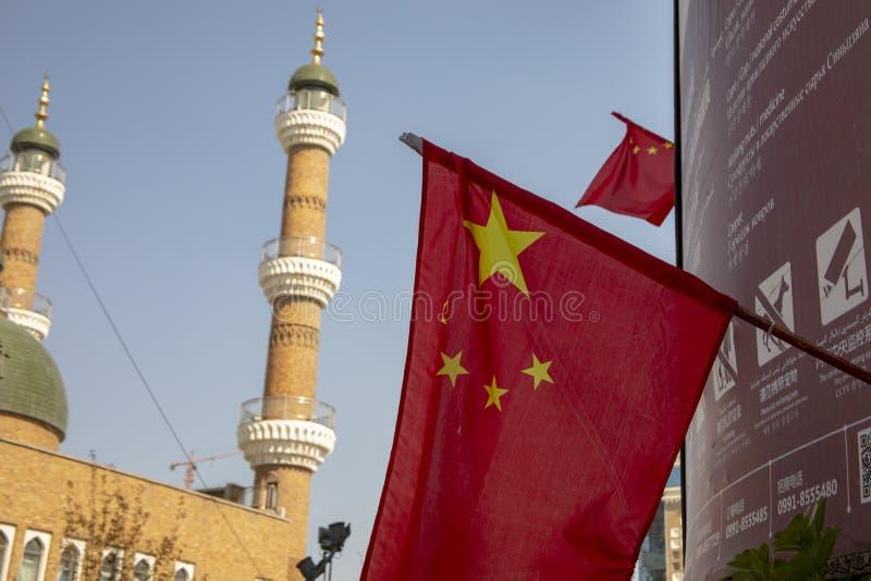Bandeira chinesa ao lado da mesquita com aviso afixado da segurança, Urumch imagens de stock royalty free