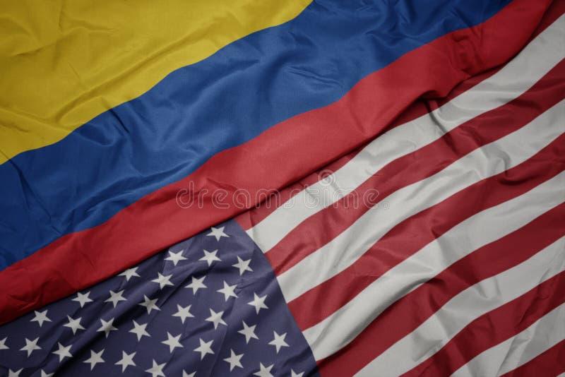 bandeira colorida de ondulação de Estados Unidos da América e bandeira nacional de Colômbia foto de stock