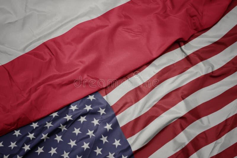 bandeira colorida de ondulação de Estados Unidos da América e bandeira nacional de poland Macro foto de stock royalty free
