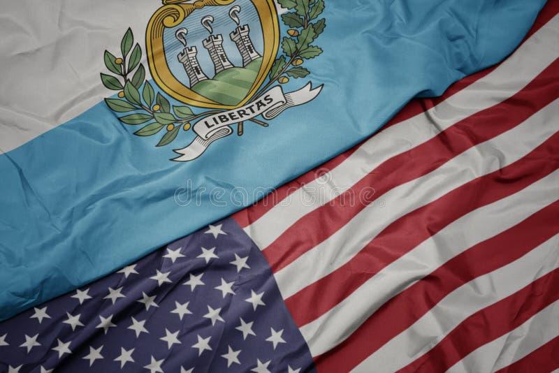 bandeira colorida de ondulação de Estados Unidos da América e bandeira nacional de San Marino Macro foto de stock royalty free