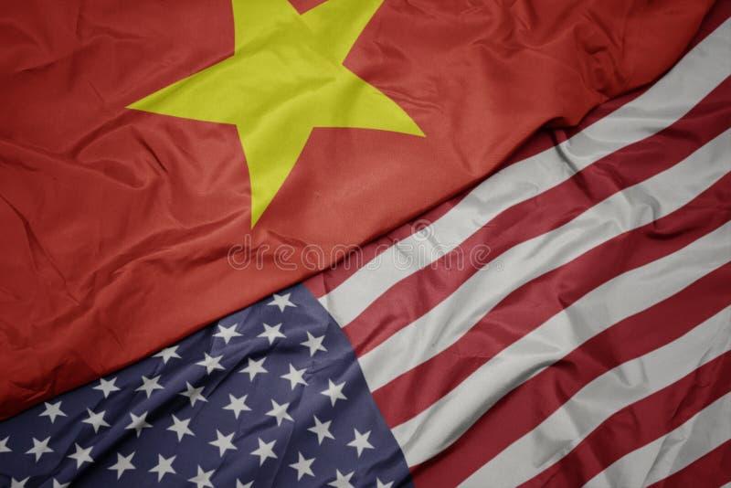 bandeira colorida de ondulação de Estados Unidos da América e bandeira nacional de Vietnam fotografia de stock