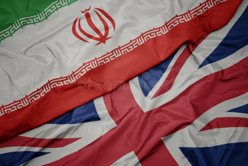 bandeira colorida de ondulação de Grâ Bretanha e bandeira nacional de Irã imagem de stock