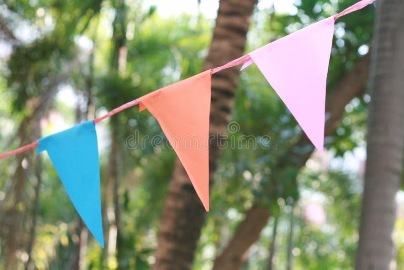 Bandeira colorida do triângulo que pendura em um partido exterior fotos de stock