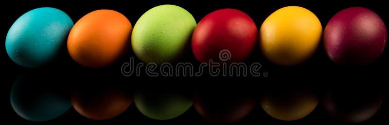 Bandeira colorida dos ovos da páscoa no fundo preto, reflexões fotos de stock