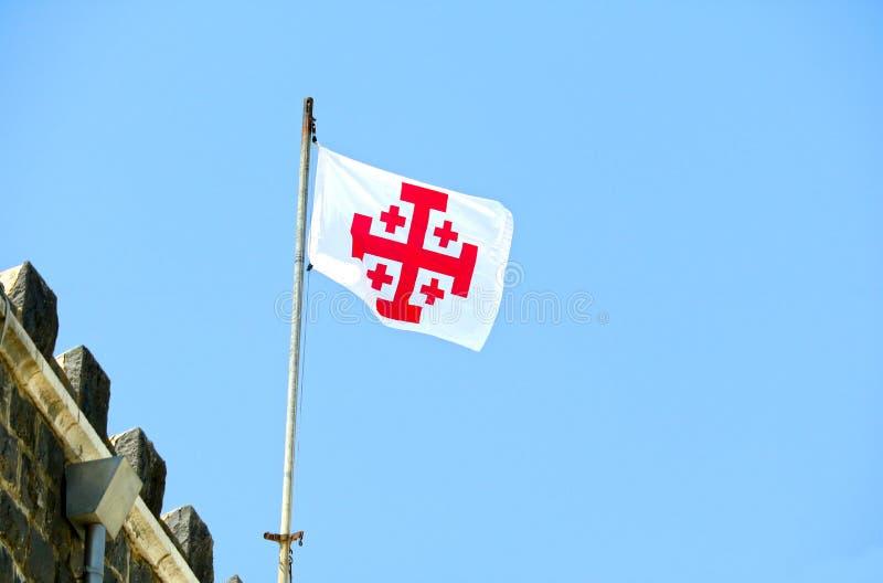 Bandeira com cruz grega no vermelho Jerusalém, Isreal O ` da cruz de Jerusalém do ` é o símbolo da custódia da Terra Santa foto de stock