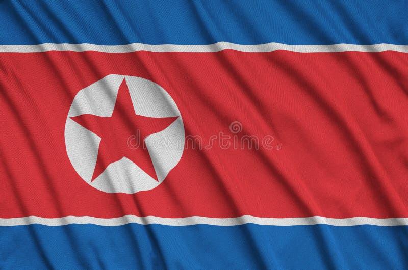 A bandeira da Coreia do Norte é descrita em uma tela de pano dos esportes com muitas dobras Bandeira da equipe de esporte fotografia de stock