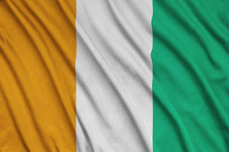 A bandeira da Costa do Marfim é descrita em uma tela de pano dos esportes com muitas dobras Bandeira da equipe de esporte foto de stock royalty free
