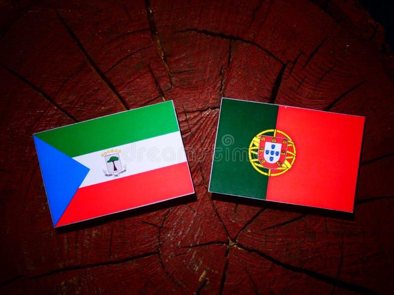 Bandeira da Guiné Equatorial com bandeira portuguesa em um isolador do coto de árvore fotos de stock