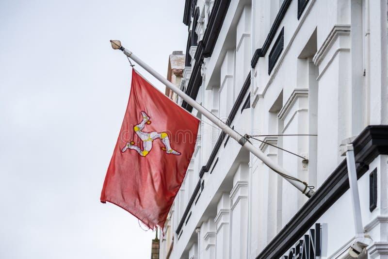 A bandeira da ilha do homem ou a bandeira de Mann são um triskelion, composto de três pés blindados com dentes retos dourados, em fotografia de stock royalty free