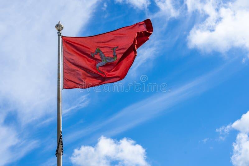 A bandeira da ilha do homem ou a bandeira de Mann são um triskelion, composto de três pés blindados com dentes retos dourados, em fotografia de stock