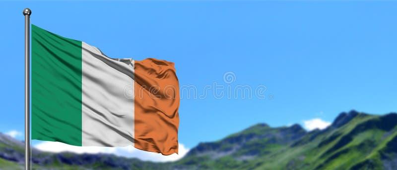 Bandeira da Irlanda que acena no céu azul com campos verdes no fundo do pico de montanha Tema da natureza foto de stock