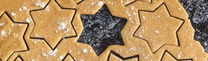 Bandeira da massa caseiro do pão-de-espécie do Natal cru desenrolada na tabela escura imagem de stock royalty free