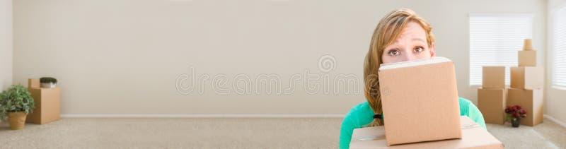 Bandeira da mulher adulta nova feliz que guarda caixas moventes em vazio fotos de stock