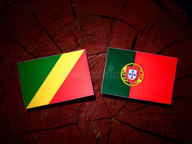 Bandeira da República Democrática do Congo com bandeira portuguesa em um coto de árvore fotos de stock