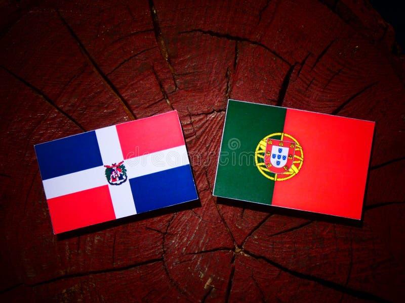 Bandeira da República Dominicana com bandeira portuguesa em um iso do coto de árvore foto de stock royalty free