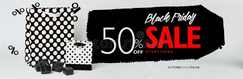 Bandeira da venda de Black Friday, com as caixas de presente pretas pequenas, e presente-sacos preto e branco com às bolinhas foto de stock