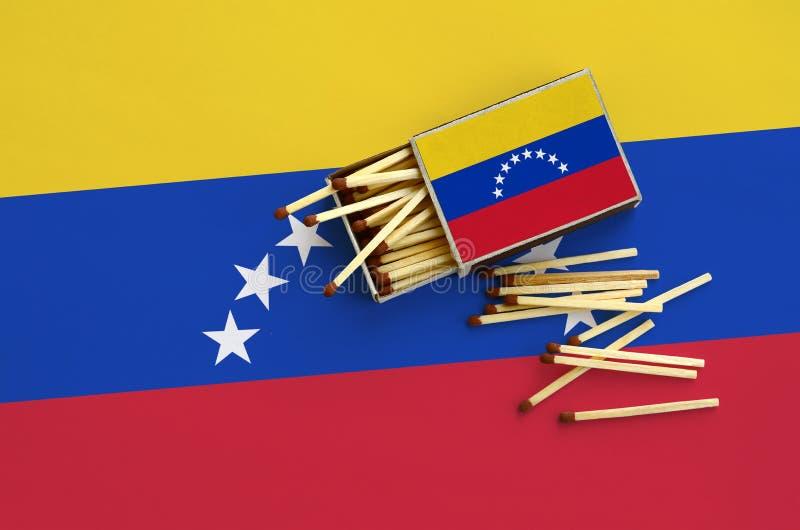 A bandeira da Venezuela é mostrada em uma caixa de fósforos aberta, de que diversos fósforos caem e mentiras em uma grande bandei fotografia de stock royalty free
