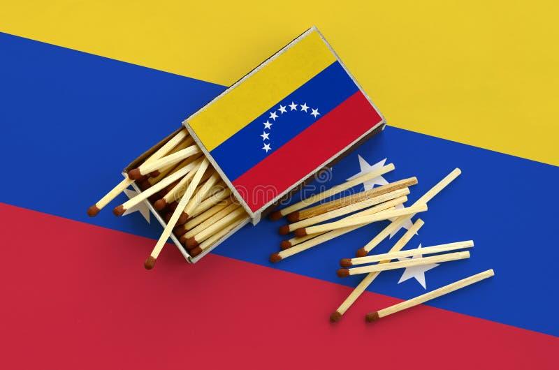 A bandeira da Venezuela é mostrada em uma caixa de fósforos aberta, de que diversos fósforos caem e mentiras em uma grande bandei foto de stock royalty free