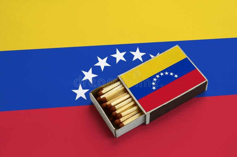 A bandeira da Venezuela é mostrada em uma caixa de fósforos aberta, que seja enchida com os fósforos e se encontre em uma grande  foto de stock royalty free