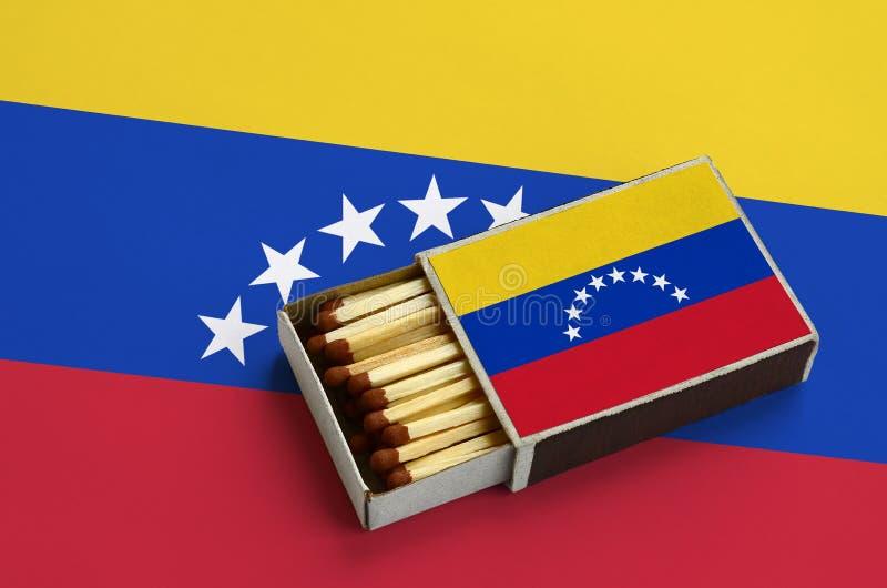 A bandeira da Venezuela é mostrada em uma caixa de fósforos aberta, que seja enchida com os fósforos e se encontre em uma grande  imagem de stock
