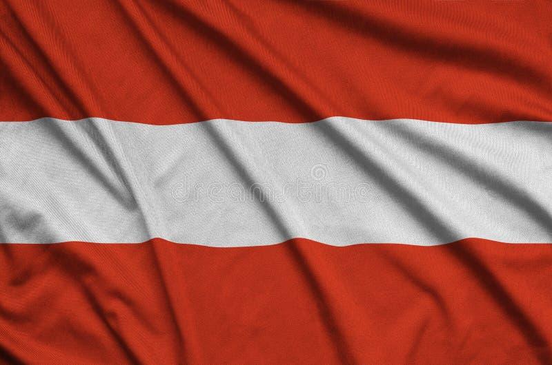A bandeira de Áustria é descrita em uma tela de pano dos esportes com muitas dobras Bandeira da equipe de esporte imagens de stock