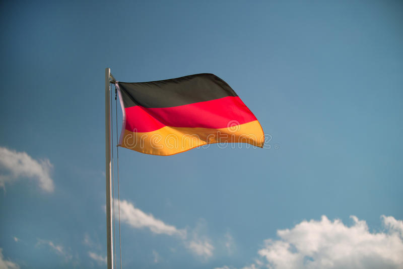 Bandeira de Alemanha na frente de um céu azul imagem de stock royalty free