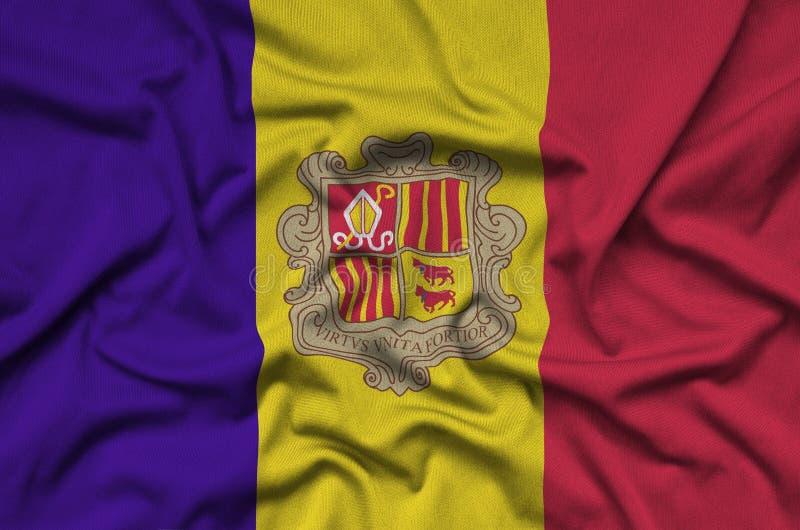 A bandeira de Andorra é descrita em uma tela de pano dos esportes com muitas dobras Bandeira da equipe de esporte foto de stock royalty free