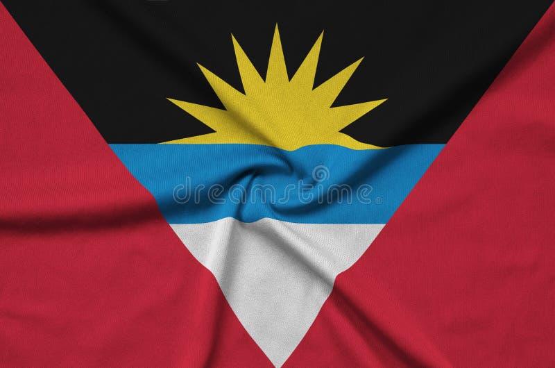 A bandeira de Antígua e Barbuda é descrita em uma tela de pano dos esportes com muitas dobras Bandeira da equipe de esporte fotografia de stock royalty free