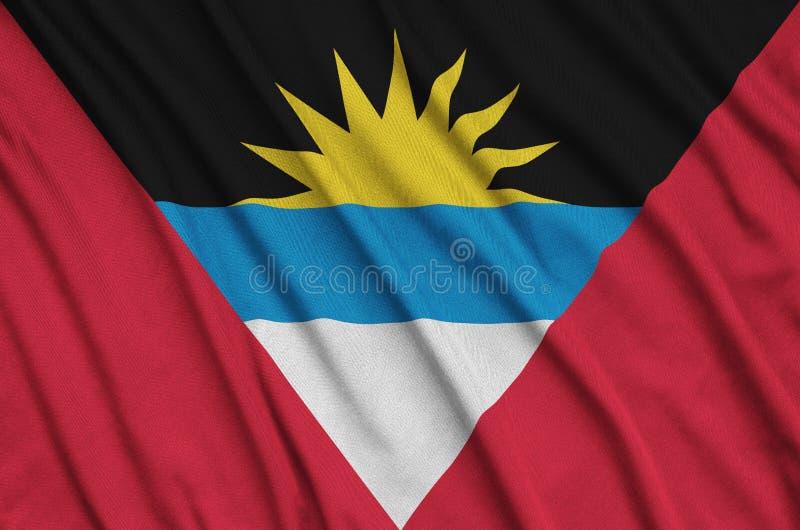 A bandeira de Antígua e Barbuda é descrita em uma tela de pano dos esportes com muitas dobras Bandeira da equipe de esporte imagens de stock