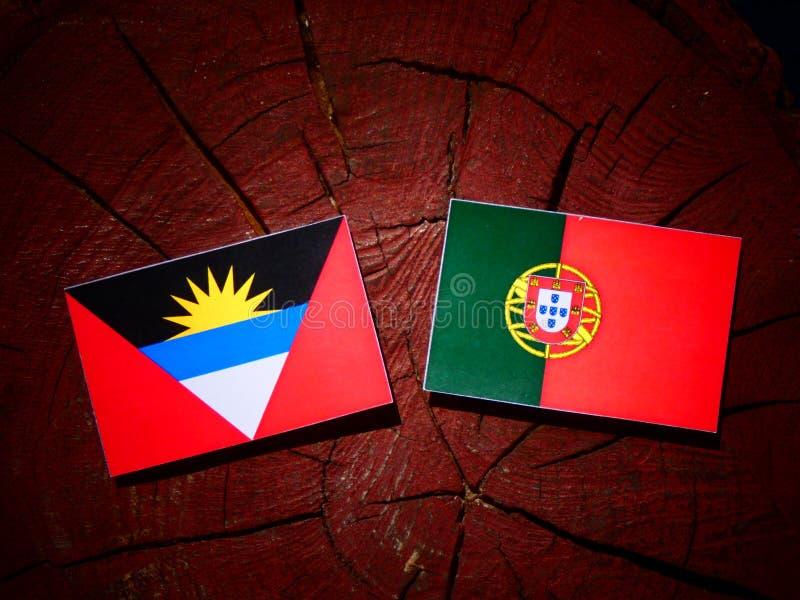 A bandeira de Antígua e Barbuda com bandeira portuguesa em um coto de árvore é imagem de stock