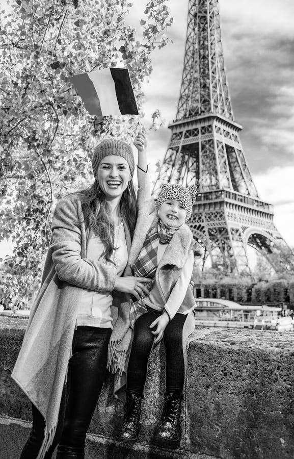 Bandeira de aumentação da mãe e da filha ao sentar-se no parapeito, Paris foto de stock