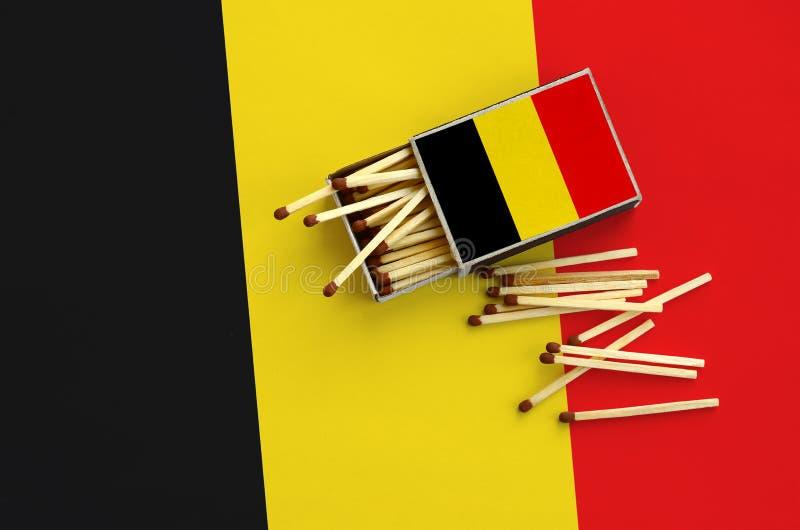 A bandeira de Bélgica é mostrada em uma caixa de fósforos aberta, de que diversos fósforos caem e mentiras em uma grande bandeira fotos de stock