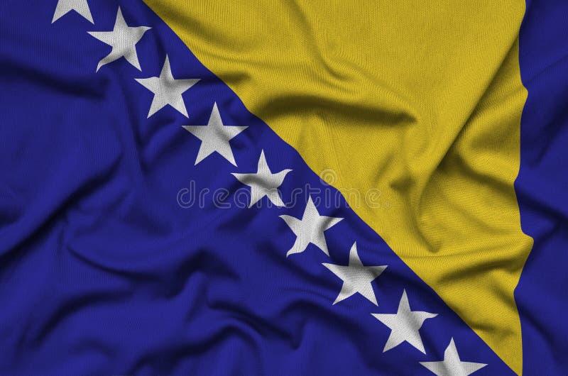 A bandeira de Bósnia e de Herzegovina é descrita em uma tela de pano dos esportes com muitas dobras Bandeira da equipe de esporte fotografia de stock royalty free
