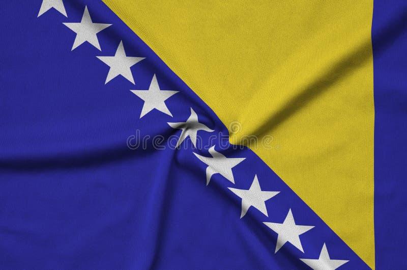 A bandeira de Bósnia e de Herzegovina é descrita em uma tela de pano dos esportes com muitas dobras Bandeira da equipe de esporte imagem de stock