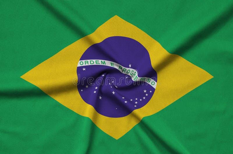 A bandeira de Brasil é descrita em uma tela de pano dos esportes com muitas dobras Bandeira da equipe de esporte fotografia de stock royalty free