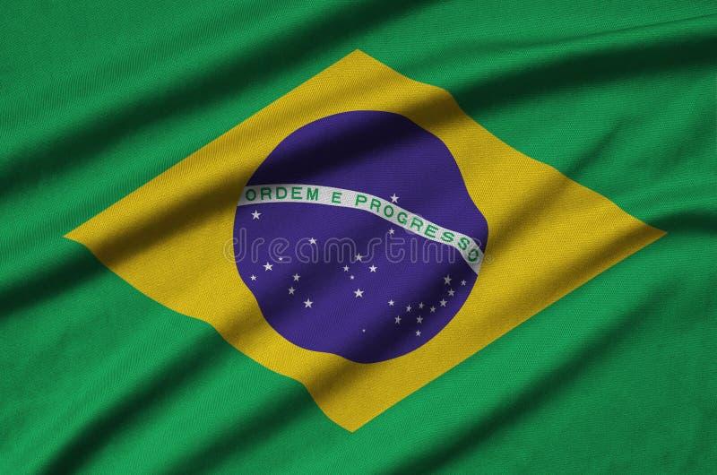 A bandeira de Brasil é descrita em uma tela de pano dos esportes com muitas dobras Bandeira da equipe de esporte fotos de stock royalty free
