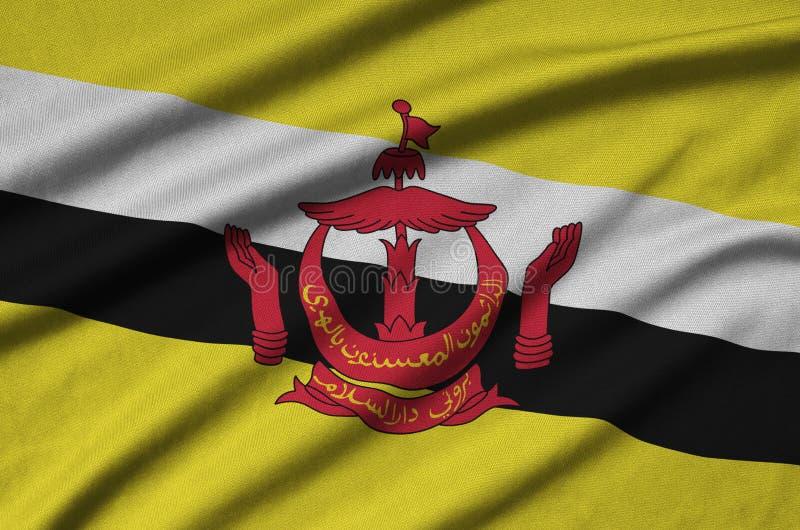 A bandeira de Brunei Darussalam Darussalam é descrita em uma tela de pano dos esportes com muitas dobras Bandeira da equipe de es imagem de stock royalty free