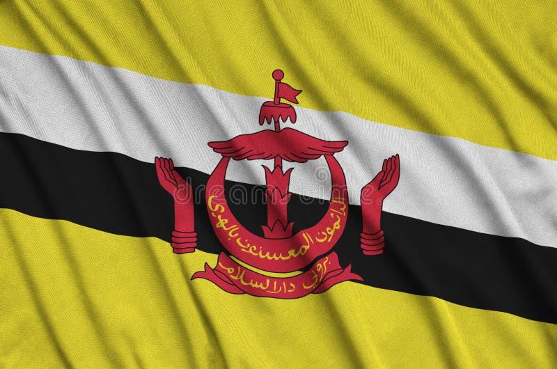 A bandeira de Brunei Darussalam Darussalam é descrita em uma tela de pano dos esportes com muitas dobras Bandeira da equipe de es foto de stock royalty free