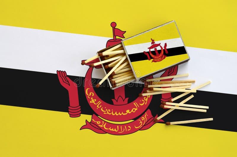 A bandeira de Brunei Darussalam Darussalam é mostrada em uma caixa de fósforos aberta, de que diversos fósforos caem e mentiras e imagens de stock