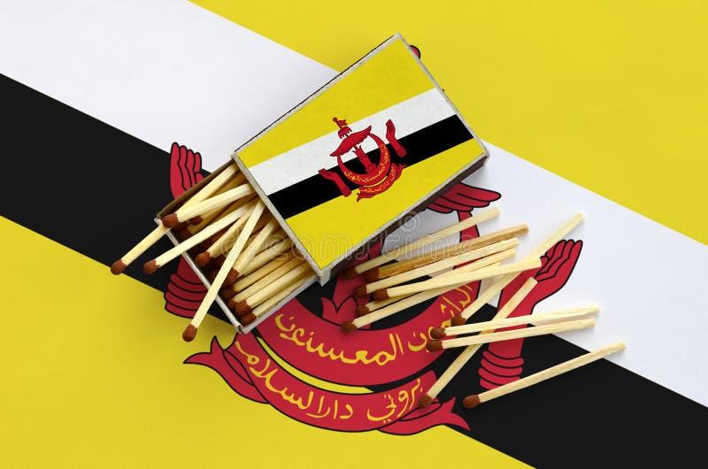 A bandeira de Brunei Darussalam Darussalam é mostrada em uma caixa de fósforos aberta, de que diversos fósforos caem e mentiras e fotos de stock
