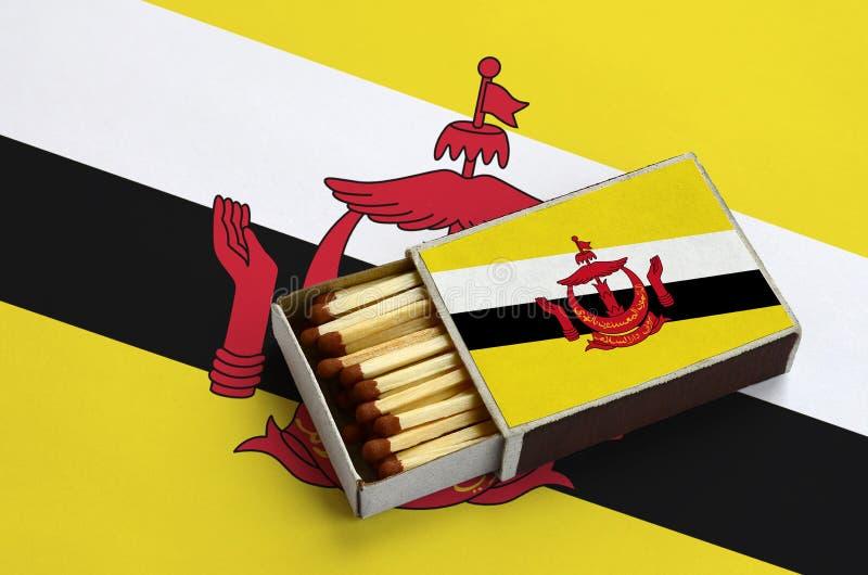 A bandeira de Brunei Darussalam Darussalam é mostrada em uma caixa de fósforos aberta, que seja enchida com os fósforos e se enco imagens de stock