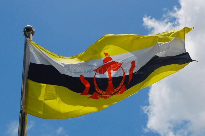 Bandeira de Brunei Darussalam em um céu azul e em um fundo nebuloso foto de stock