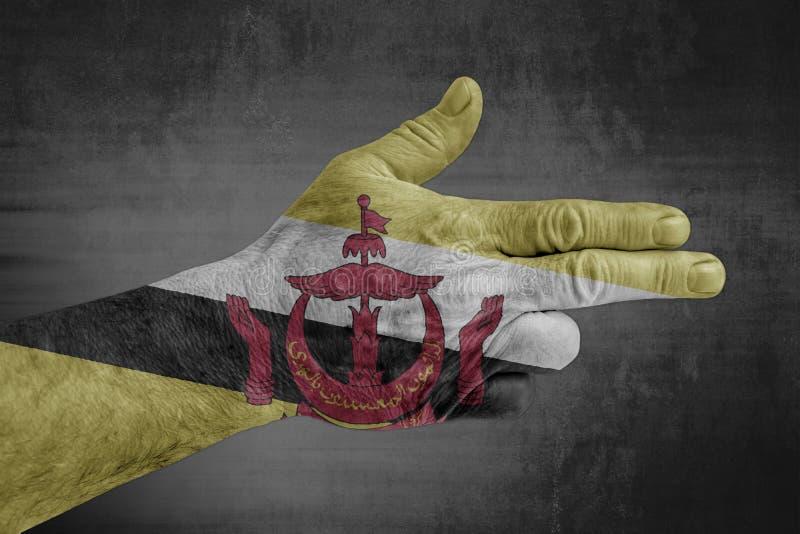 Bandeira de Brunei Darussalam pintada na mão masculina como uma arma imagem de stock royalty free