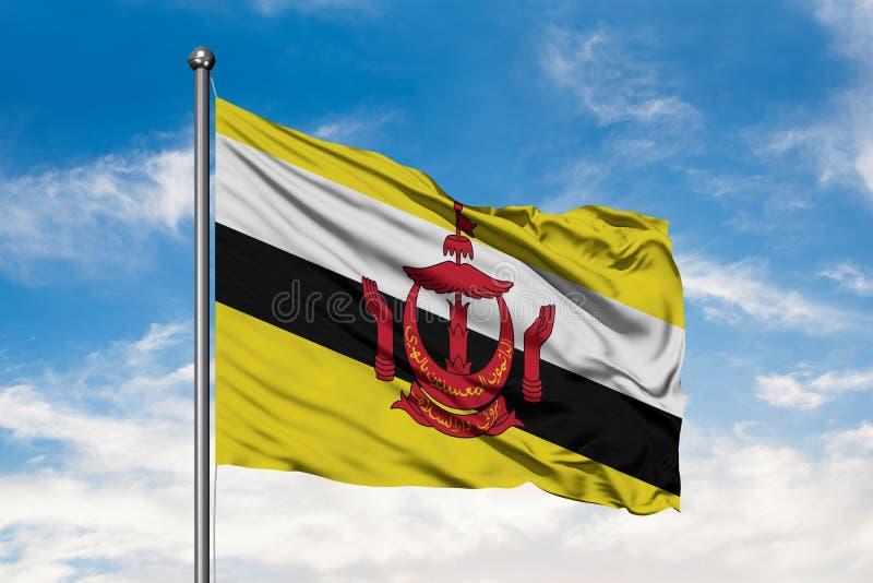 Bandeira de Brunei Darussalam que acena no vento contra o céu azul nebuloso branco Bandeira Bruneian foto de stock