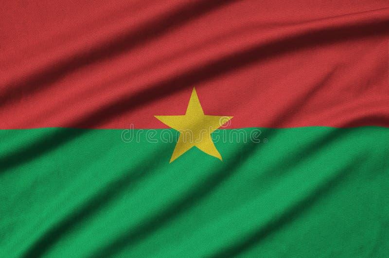 A bandeira de Burkina Faso é descrita em uma tela de pano dos esportes com muitas dobras Bandeira da equipe de esporte fotografia de stock royalty free
