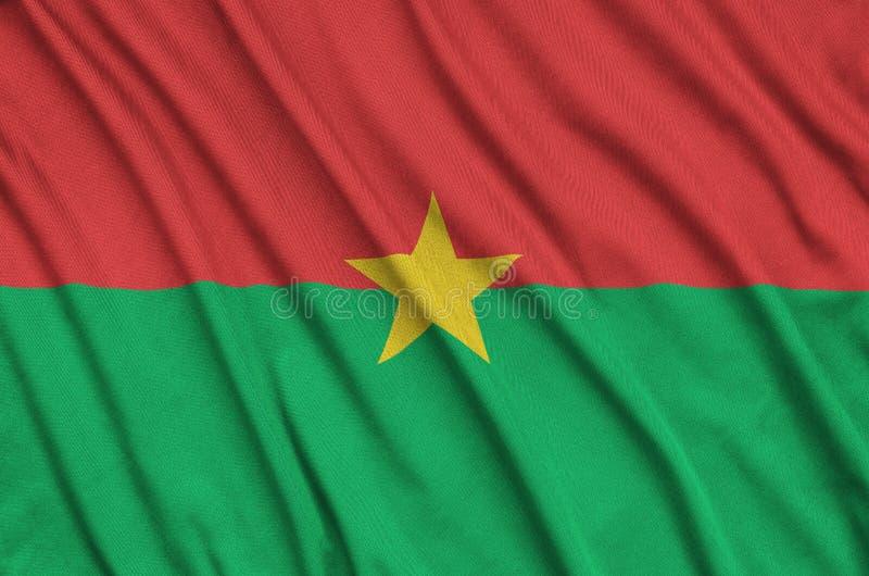 A bandeira de Burkina Faso é descrita em uma tela de pano dos esportes com muitas dobras Bandeira da equipe de esporte foto de stock royalty free