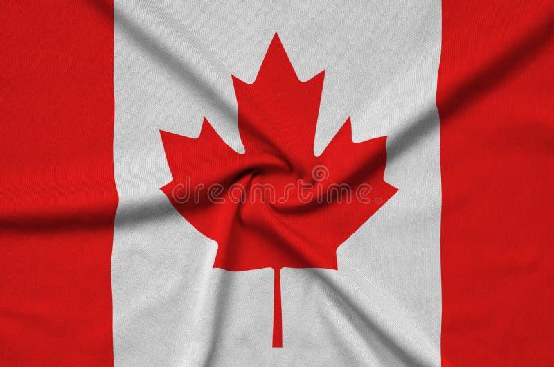 A bandeira de Canadá é descrita em uma tela de pano dos esportes com muitas dobras Bandeira da equipe de esporte fotos de stock royalty free