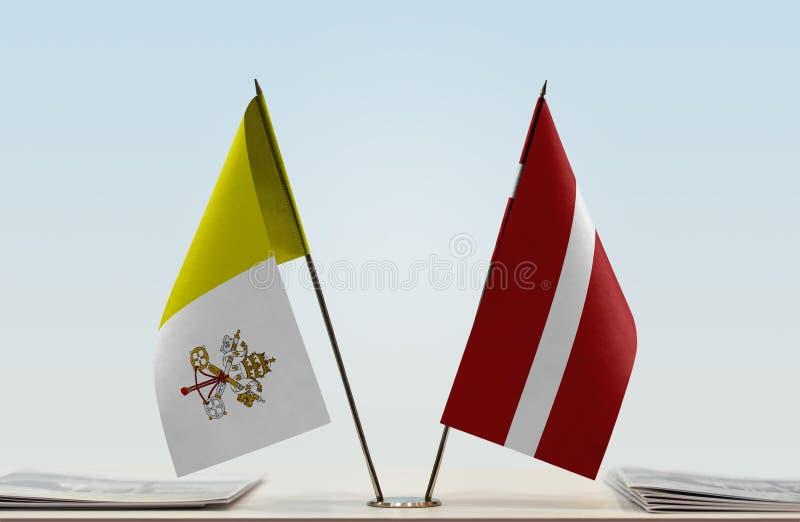 Bandeira de Cidade Estado do Vaticano e de Letónia fotos de stock royalty free